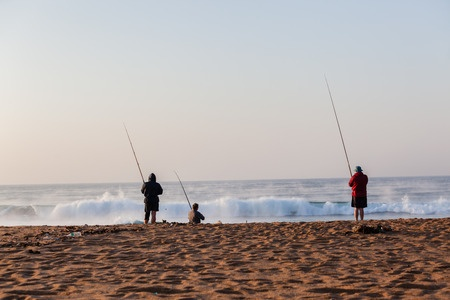 family surf fishing on the beach
